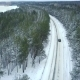 Flying Above Car Driving on a Winding Road Passing through the Snowy Winter Forest - VideoHive Item for Sale