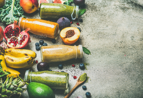 Colorful smoothies in bottles with fresh fruits, copy space - Stock Photo - Images