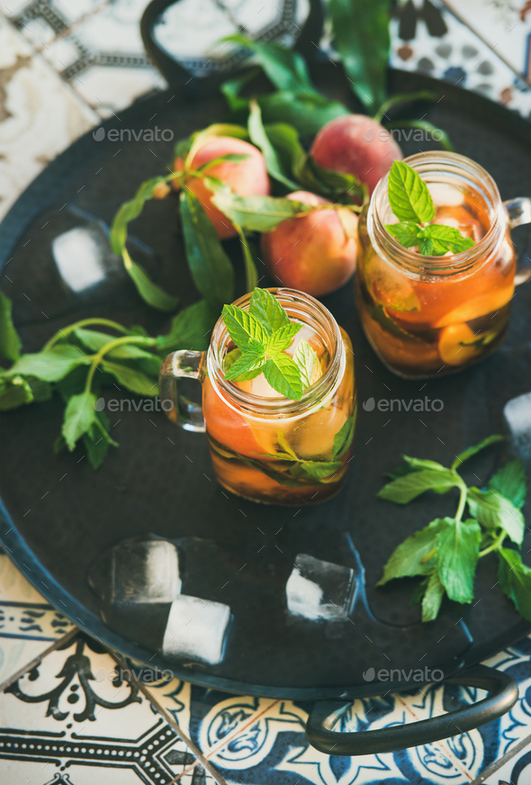 Summer refreshing cold peach ice tea in glass jars - Stock Photo - Images