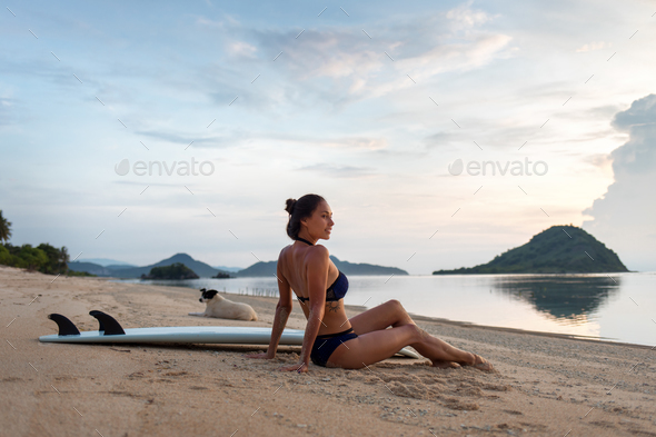 smiling happy sporty girl or woman chilling on sandy coast - Stock Photo - Images