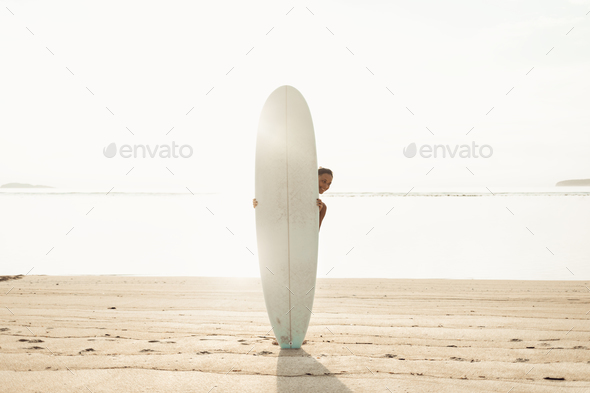 sun-tanned happy brunette (girl, woman, tourist) standing behing surfboard - Stock Photo - Images