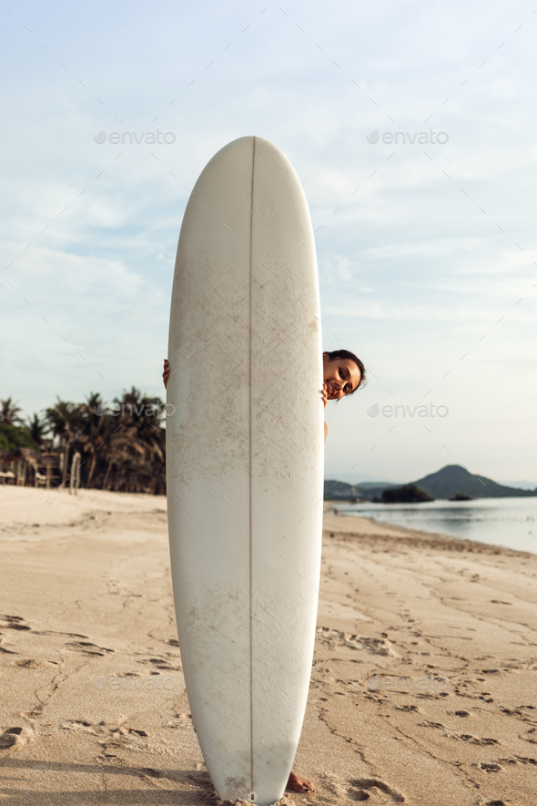 smiling naked girl or woman hiding behind white surfboard on sandy sunny beach - Stock Photo - Images