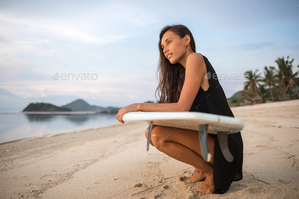 smiling happy excited active girl or woman holding surfboard - Stock Photo - Images