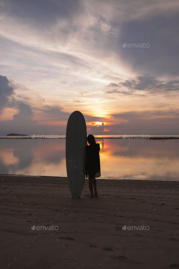sporty girl or woman standing on sandy beach in the evening, sunset time - Stock Photo - Images