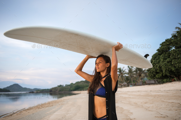 pretty sporty girl or woman in shape going to surf - Stock Photo - Images