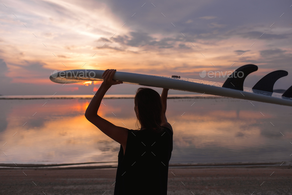 young woman or girl surfer on the beach looking at water - Stock Photo - Images