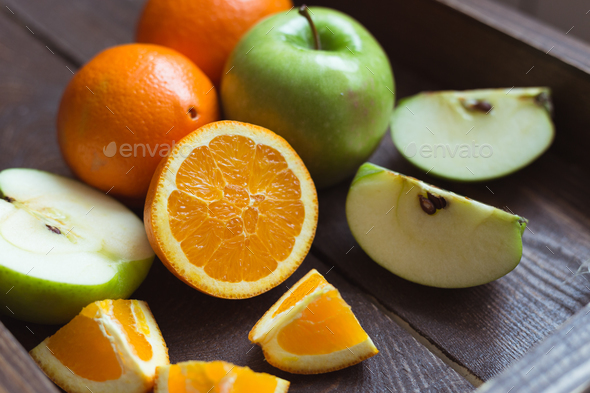 Apple and orange on the wooden tray - Stock Photo - Images