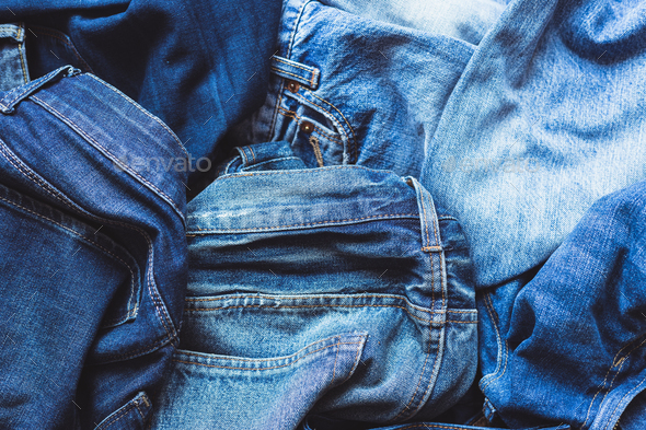 Jeans scattered on a wooden background - Stock Photo - Images