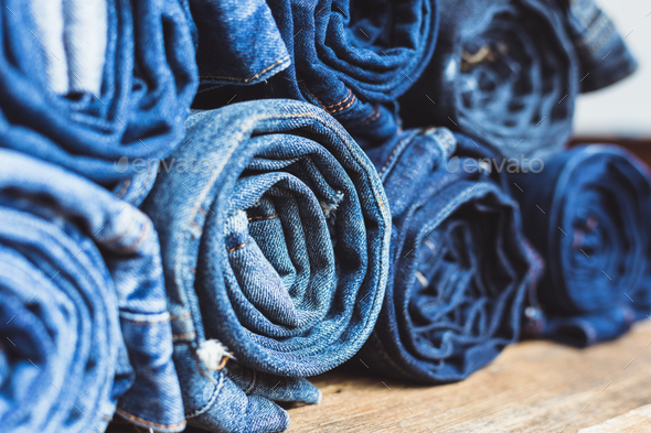 Jeans stacked on a wooden background - Stock Photo - Images