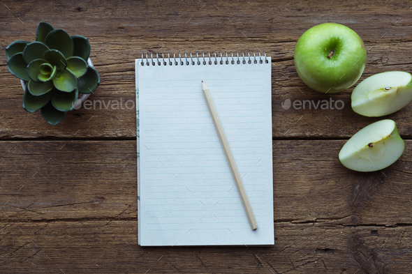 Top view of green apple, notepad and pencil on wooden background - Stock Photo - Images