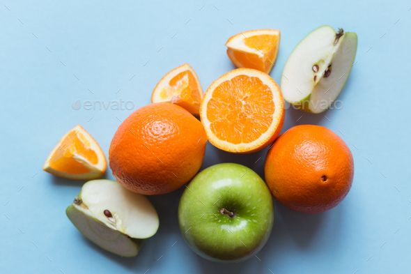 Fresh oranges and green apples on the blue background - Stock Photo - Images