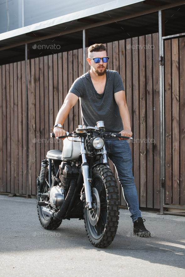 Rider guy with classic style cafe racer motorcycle - Stock Photo - Images