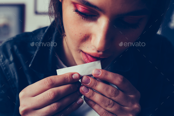 young beautifil girl with makeup licking cigarette paper - Stock Photo - Images