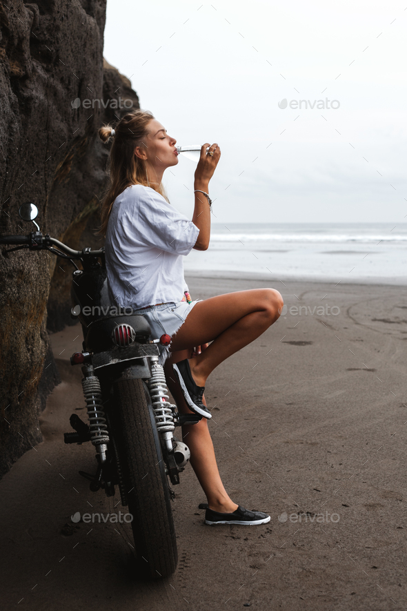 thursty young girl sitting on the motorbike and drinking water - Stock Photo - Images
