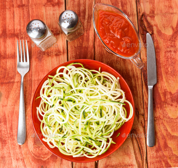 serving of raw zucchini spaghetti on wooden board - Stock Photo - Images