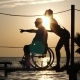 Lucky Disabled with Girlfriend Look Into Distance and Shows His Arms To Horizon on Background Sunset - VideoHive Item for Sale
