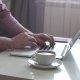 A Person Works From Home Using the Top and Trackpad. Young Business Man Sitting at Table Drinking
