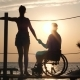 Girl with Friend Handicapped Holding Hands Stand on Pier and Look at Sunset - VideoHive Item for Sale