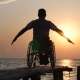 Diseased Man in Wheelchair Relaxes and Lift His Hands Backdrop of Orange Sky on Summer Trip - VideoHive Item for Sale