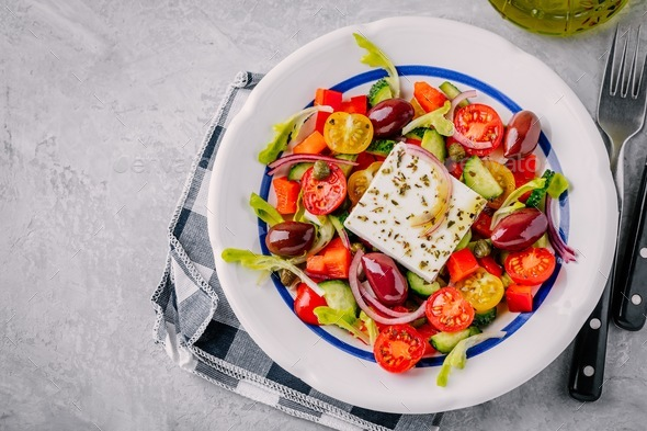 Delicious Greek salad with feta cheese, olives, tomatoes, cucumbers, paprika and red onions. - Stock Photo - Images