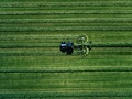 Blue tractor mowing green field, aerial view - PhotoDune Item for Sale
