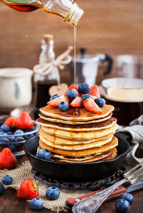 Stack of freshly prepared banana  pancakes with fresh berries - Stock Photo - Images