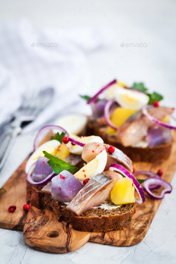 Open sandwich (smorrebrod) with herring, onion, potato and eggs - Stock Photo - Images