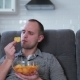 A Man Watches TV and Eats Chips - VideoHive Item for Sale