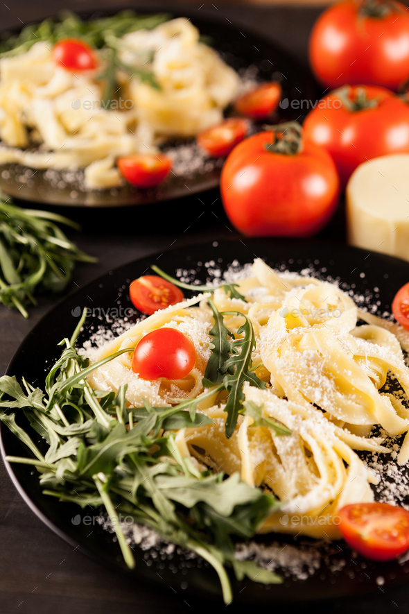 Plate with tagliatelle pasta, cherry tomatoes and greenery - Stock Photo - Images