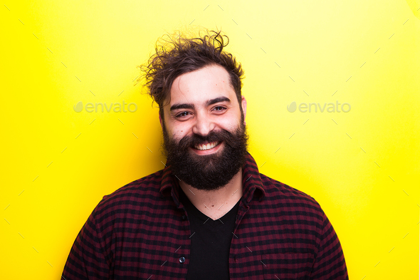 Happy smiling bearded hipster man on yellow background - Stock Photo - Images
