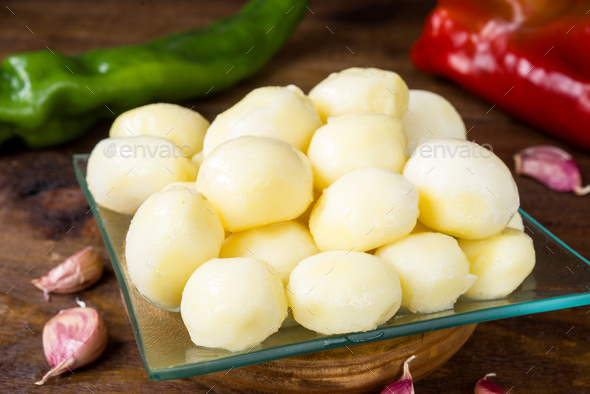 group of potatoes on crystal tray green pepper and garlics , illuminated in studio on rustic wooden - Stock Photo - Images