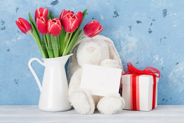 Red tulip flowers and easter rabbit toy - Stock Photo - Images