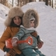 Young Mother and Little Daughter Having Fun on Sledge in Winter Park - VideoHive Item for Sale