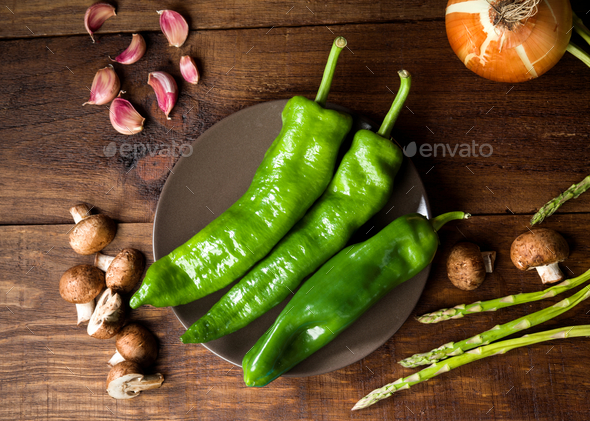 overhead take of whole raw peppers and other ingredients on rustic wood - Stock Photo - Images
