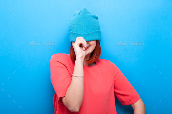 Happy smiling and laughing cool teenager girl wearing a blue hat - Stock Photo - Images