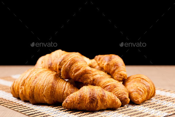 Freshly baked croissants lying on a table - Stock Photo - Images