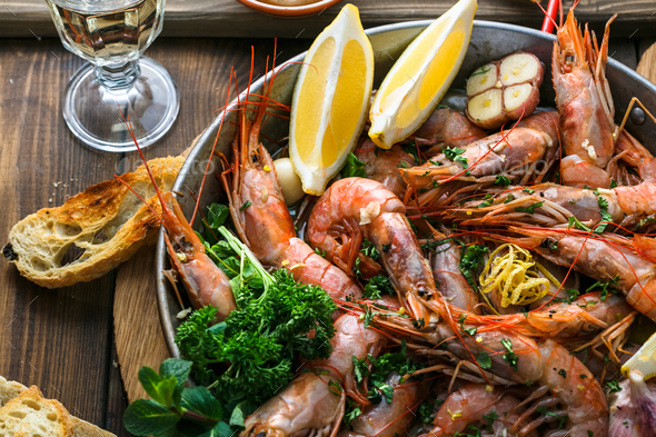 Tasty shrimps with garlic, lemoc, bread and wine - Stock Photo - Images
