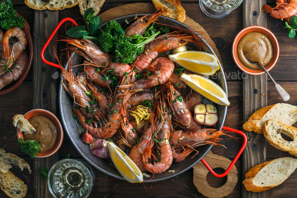 Top view of scampi in a pan with garlic and lemon. - Stock Photo - Images