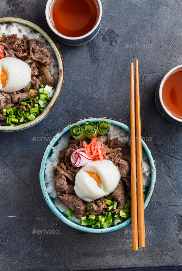 Close view of beef and rice bowl topped with egg and onion - Stock Photo - Images