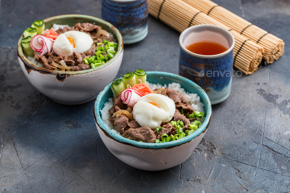 Rice and beef bowls with tea, concrete background - Stock Photo - Images