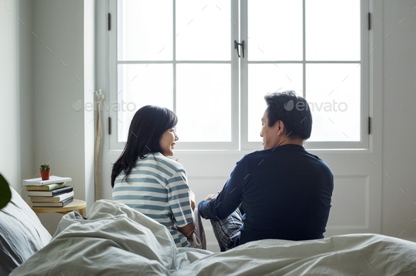 Asian couple talking together in bed - Stock Photo - Images