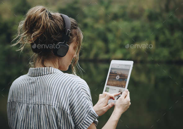 Woman alone in nature listening to music with headphones - Stock Photo - Images