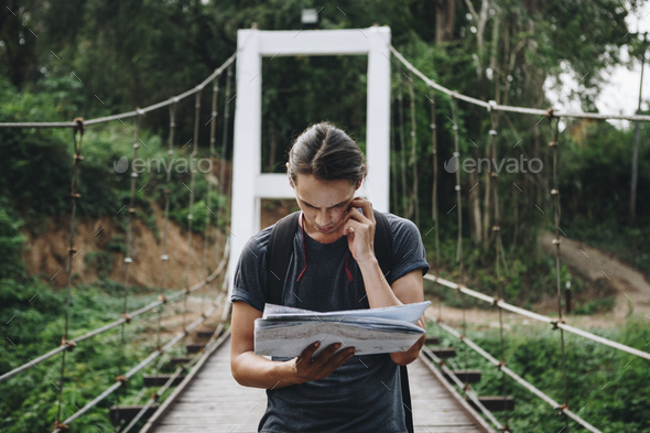 Confused Caucasian man looking at a map travel and explore concept - Stock Photo - Images