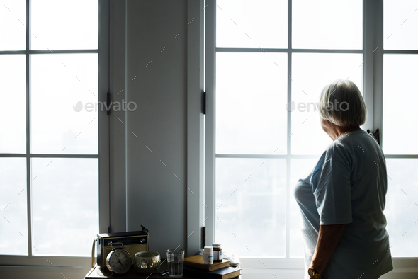 Senior woman standing alone at home - Stock Photo - Images