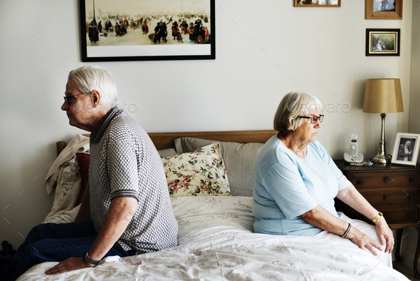 Senior couple sitting back to back - Stock Photo - Images