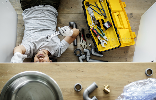 Man fixing kitchen sink - Stock Photo - Images