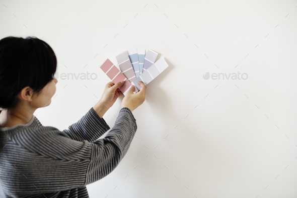 Asian woman choosing wall color - Stock Photo - Images