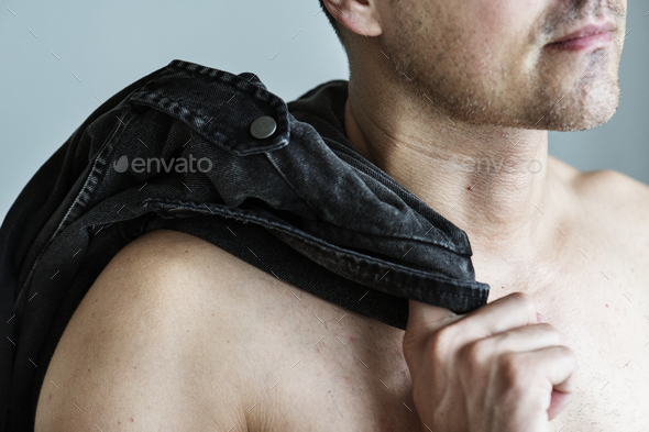 Close up of naked man with his clothes slinging on his shoulder - Stock Photo - Images