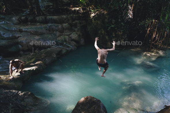 Man jumping into a natural pond - Stock Photo - Images