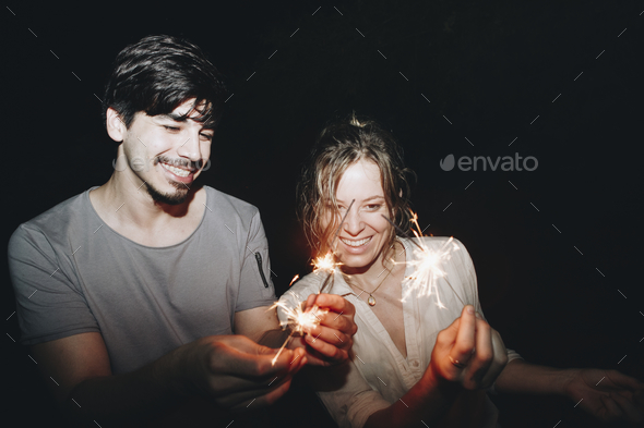 Caucasian man and woman couple playing with sparklers celebration and festive party concept - Stock Photo - Images